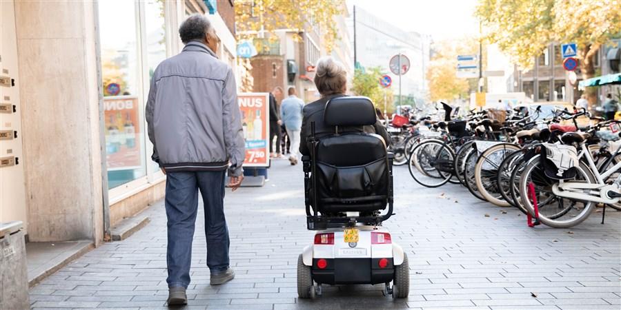 een ouder stel waarvan de vrouw in een scootmobiel zit die over de straat lopen
