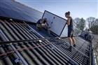 Op het dak van een stal van een boerderij worden zonnepanelen gelegd