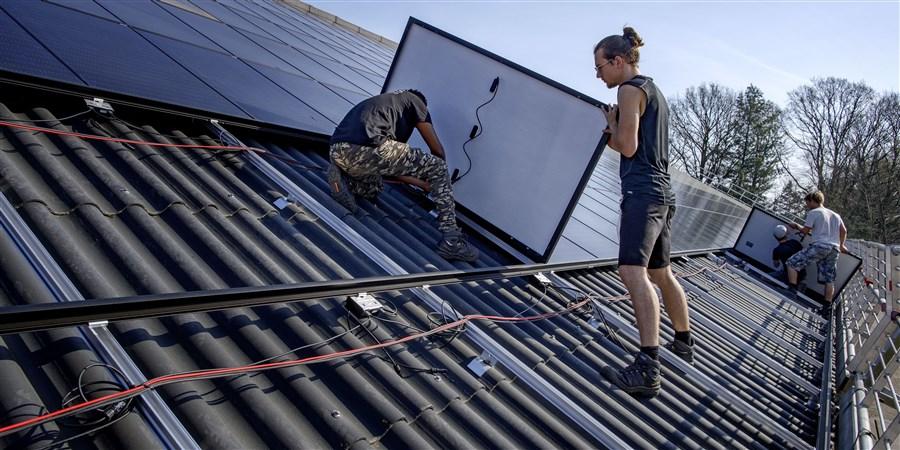Op het dak van een stal van een boerederij worden zonnepanelen gelegd