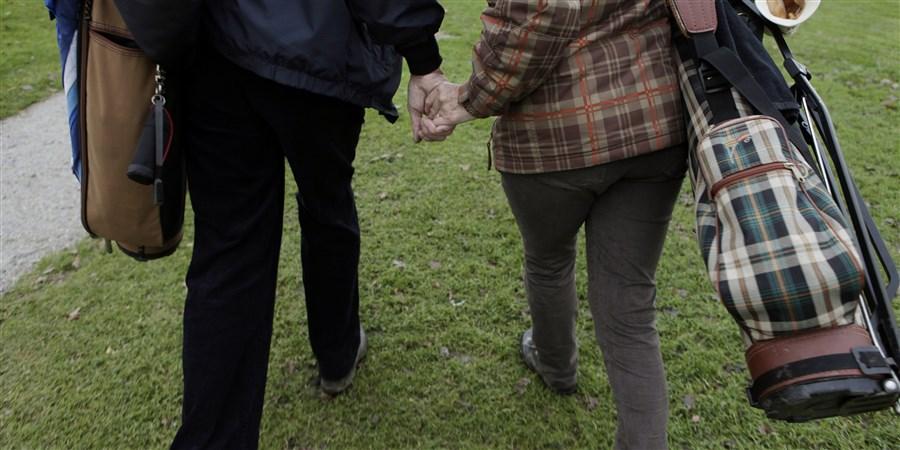Ouder echtpaar hand in hand op de golfbaan