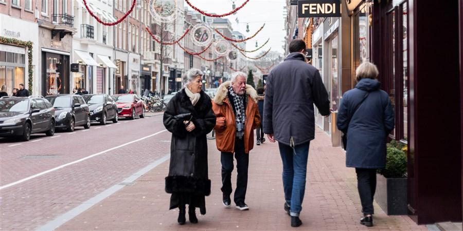 Een ouder stel loopt over een stoep in de PC Hooftstraat