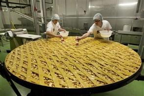 Bakkers brengen eigeel aan op de grootste appeltaart ter wereld