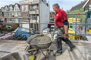 Oudere metselaar brengt kruiwagen vol met specie naar werkplek