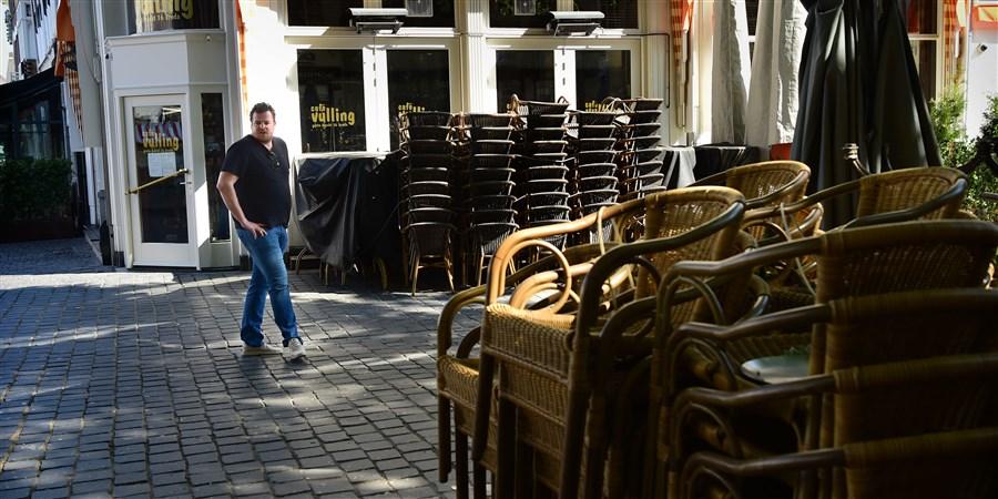 Een man loopt langs een terras met opgestapelde stoelen