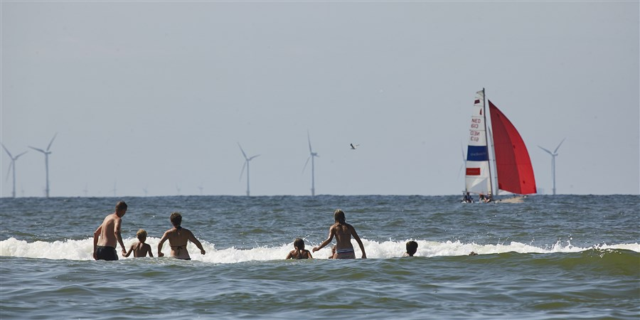 Mensen in de zee met tegen de achtergrond windmolenpark