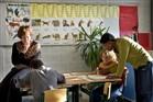 Een onderwijzeres en een onderwijsassistent (L) helpen enkele leerlingen bij hun werk op school.