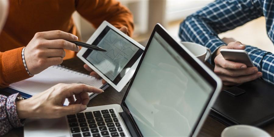 collega's die op laptop, ipad en telefoon aan het werk zijn.