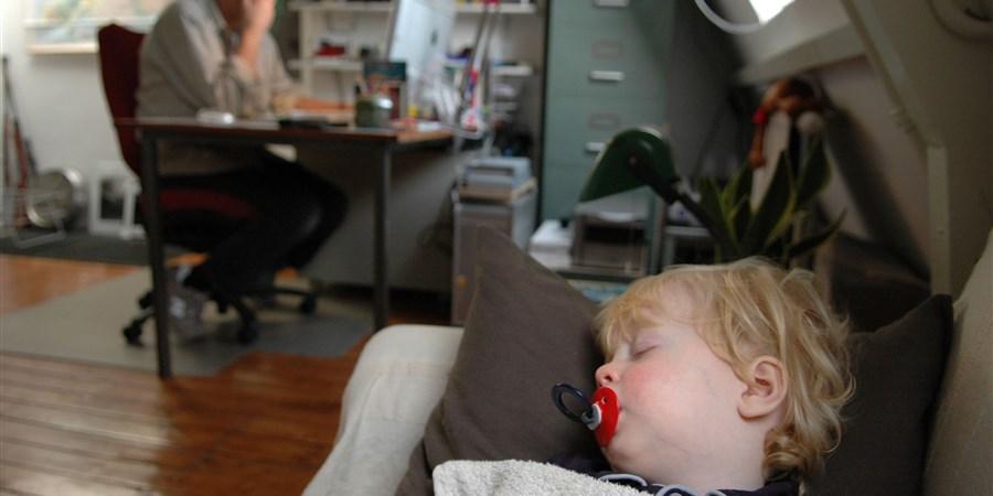 Nederland, Haarlem 20 december 2004 Ziek kind (1,5 jaar) slaapt met speen op de bank, vader werkt thuis.