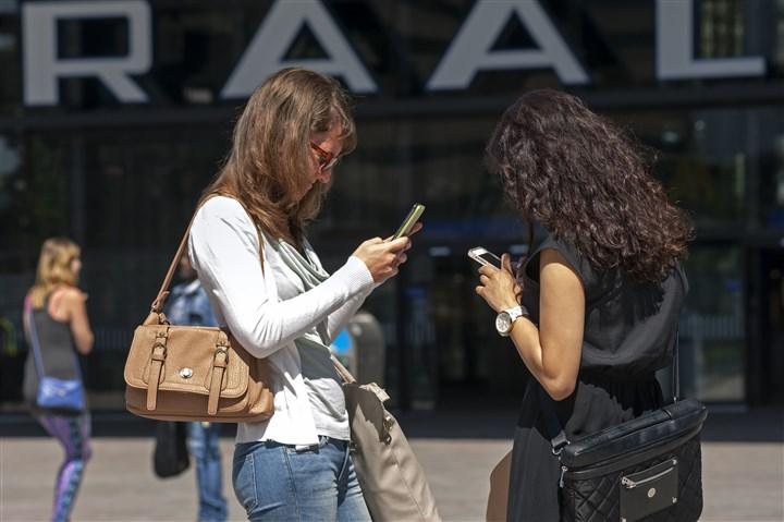 foto met meisjes die een mobiel vasthouden