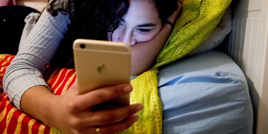 Tienermeisje achter haar mobile telefoon terwijl ze op bed ligt