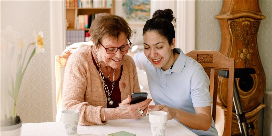 Hulpverlener helpt oudere met mobiele telefoon