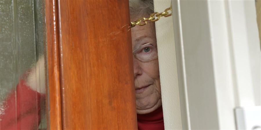 Een oudere dame kijkt door een deels geopende voordeur die op een ketting zit