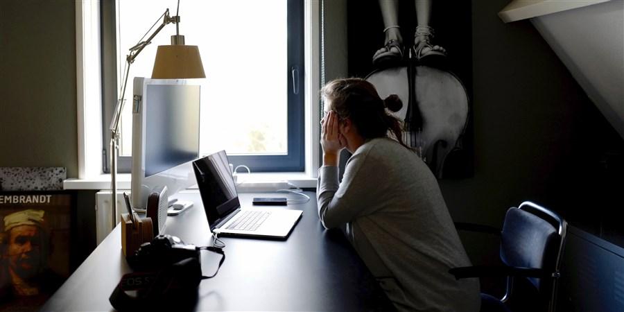Jonge vrouw aan naar bureau ziet het even niet meer zitten allemaal.