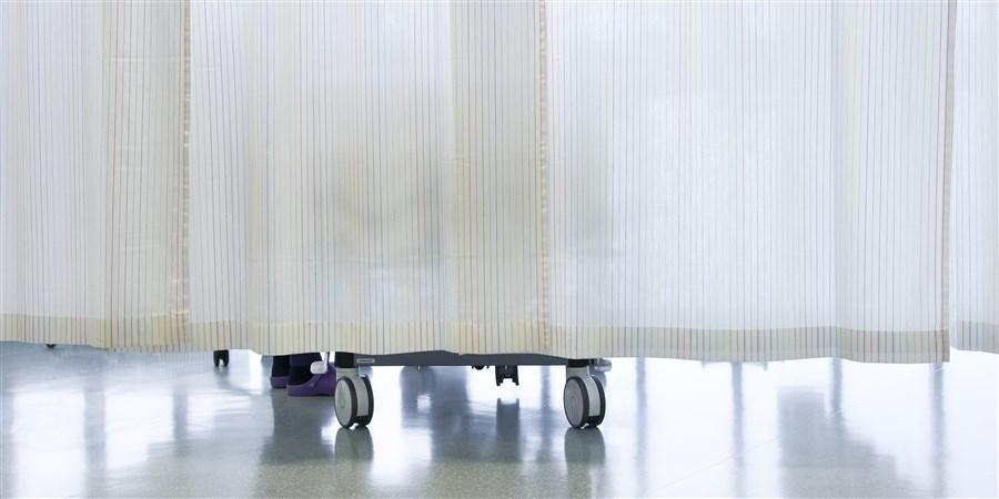 ziekenhuisbed achter deels doorschijnend gordijn