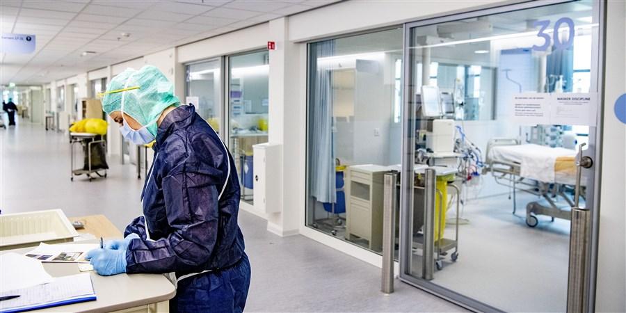Zorgmedewerker met beschermende kleding vult formulier in op de intensive care afdeling van het ziekenhuis waar coronapatiënten worden geholpen aan hun klachten.