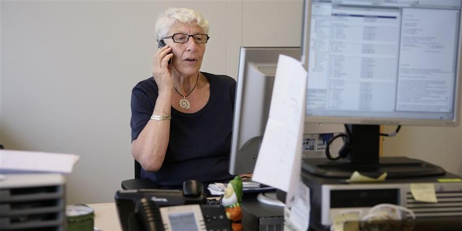 Oude vrouw aan het werk achter de computer