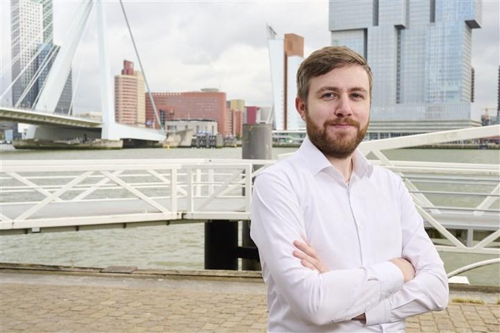 Patrick van der Reijden, statistisch onderzoeker op de Willemskade in Rotterdam, met Erasmusbrug op de achtergrond