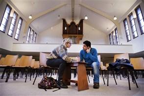 Vrouw en vluchteling in gesprek met elkaar in Noorderkerk, Zaandam