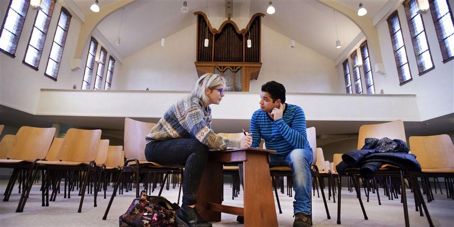 Vrouw en vluchteling in gesprek met elkaar in Noorderkerk