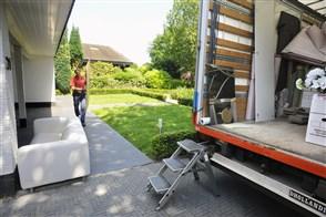 Een verhuizer laadt spullen in een verhuiswagen