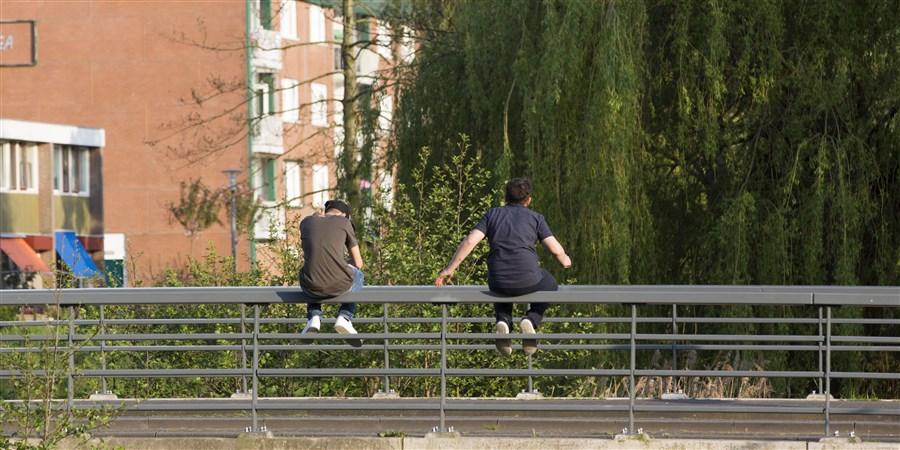 Jongeren op leuning brug