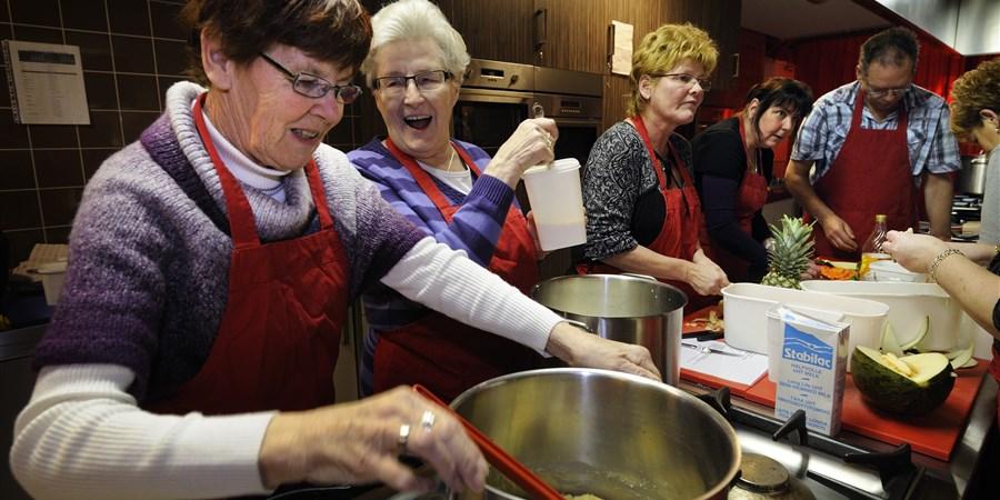 Lachende ouderen dames aan het koken