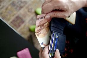 Iemand haalt een bankbiljet van 10 euro uit een portefeuille