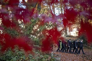 Door rode herfstbladeren heen is een uitvaart te zien op begraaf- en gedenkpark Heilig Land Stichting, een begraafplaats in het Gelderse dorp Heilig Landstichting.