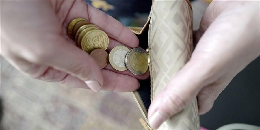Handen die kleingeld in een portemonnee doen