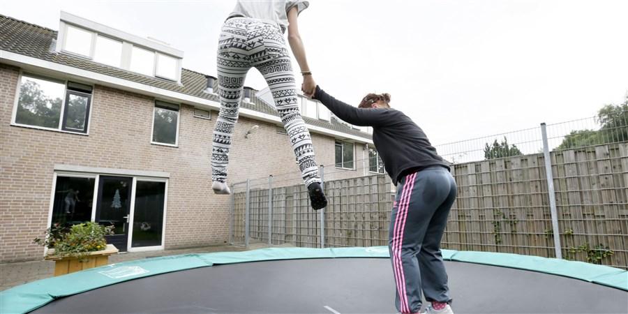 Twee meiden van internaat Lievenshove op de trampoline in de tuin