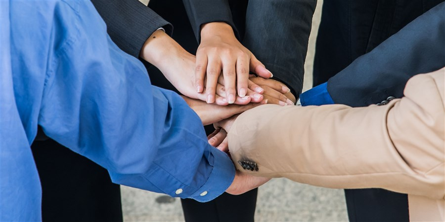 een groepje mensen slaan de handen in elkaar