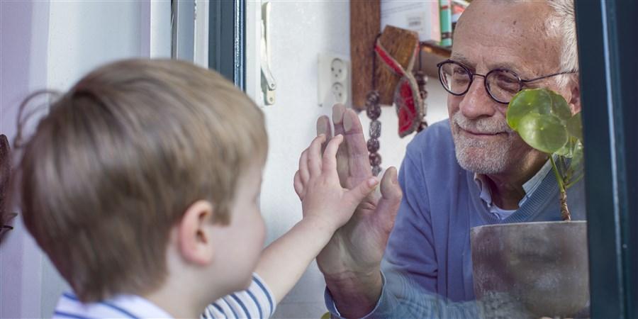 foto Opa kijkt door raam naar kleinkind