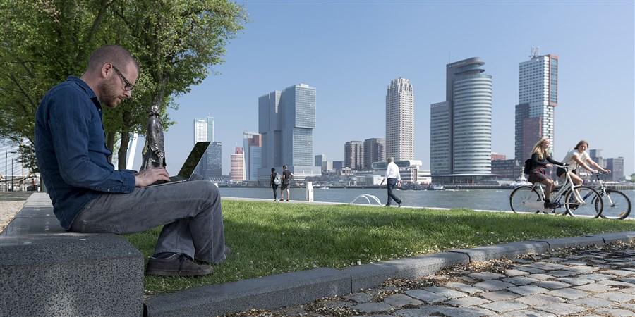 Man werkend op laptop met business center rotterdam op achtergrond