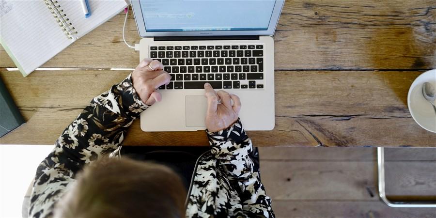Bovenaanzicht van een vrouw werkend aan een laptop op de eettafel