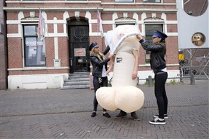 Medewerksters van de GGD verkleed als politievrouw arresteren een wandelende penis die zonder condoom door Leiden loopt tijdens een campagne voor safe seks gericht op studenten.