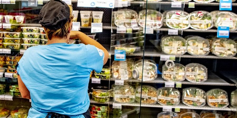 Supermarktmedewerkster vult vakken bij