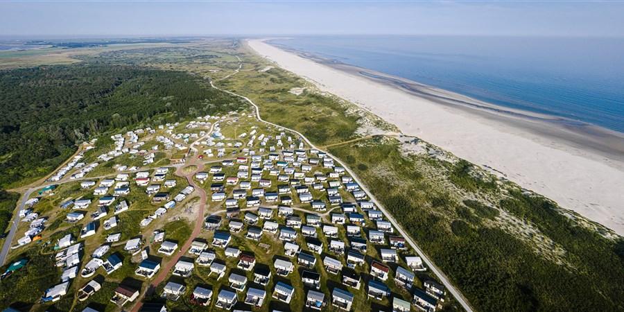 Een camping annex vakantiepark met huurhuisjes en stacaravans achter de duinen