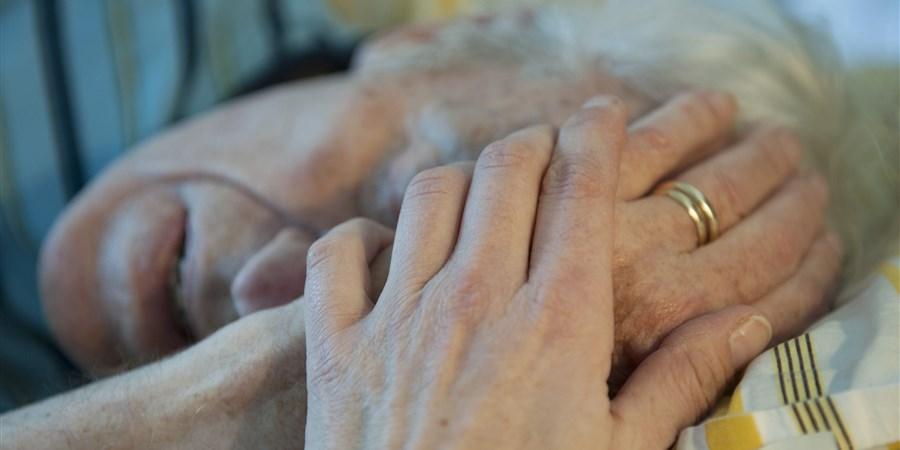 Bejaarde man ligt op sterven in zijn bed. Aan zijn ringvinger twee ringen, eentje van zijn overleden vrouw. Een familielid neemt afscheid