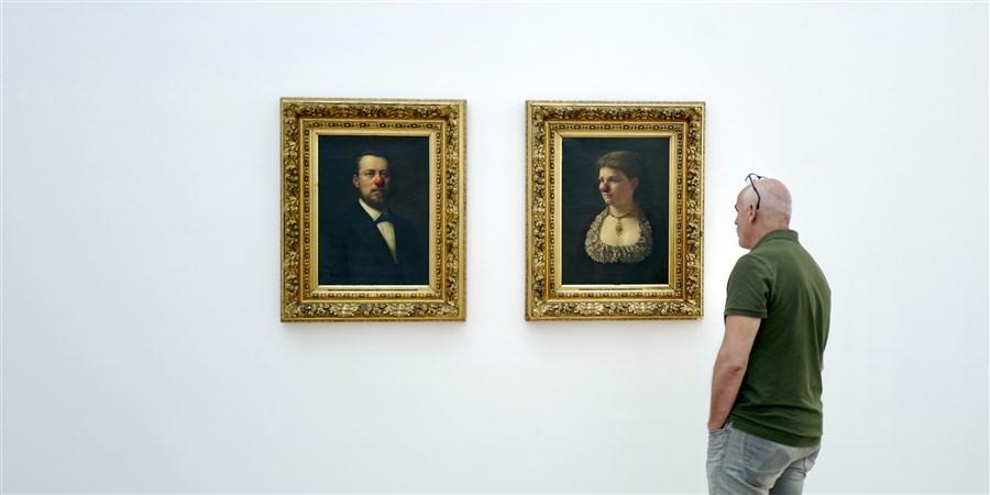 Bezoeker bekijkt twee schilderijen in een museum