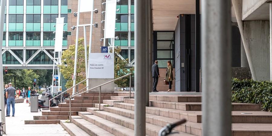 Een beeld van de voorkant van het paleis van justitie waar twee mensen in gesprek zijn met elkaar