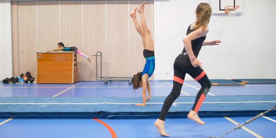 Twee meisjes aan het turnen in een Turnhal
