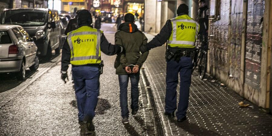 Een jongere wordt geboeid meegenomen door drie politie agenten
