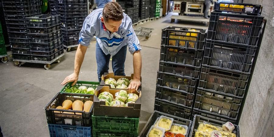 Een supermarktmedewerker is bezig met het aanvullen van de voorraden