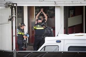 Een verdachte word gefouilleerd na zijn arrestatie tijdens een politie-inval bij theehuis