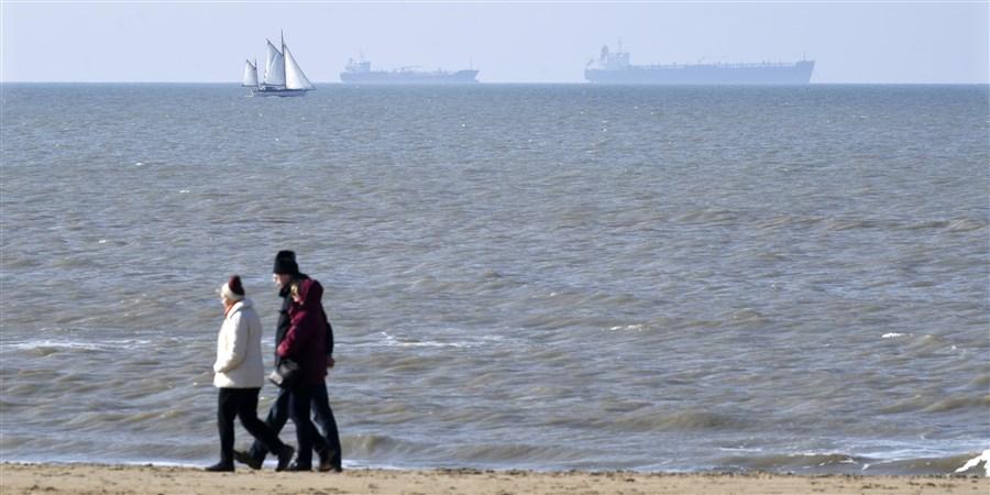 Mensen lopen langs de kust