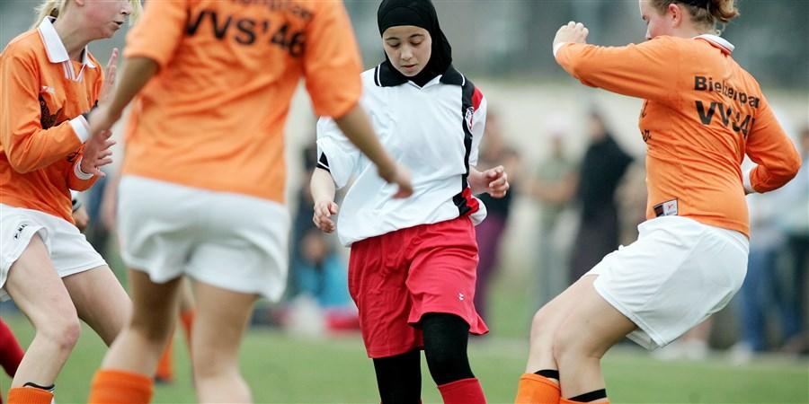 Marokkaanse vrouw voetbalt met hoofddoekje en bedekte benen tegen vrouwenteam