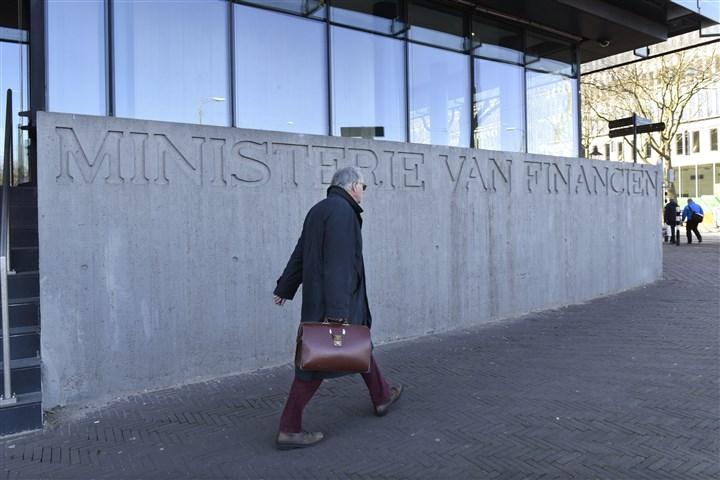 Man met tas loopt langs gebouw van het ministerie van financiën