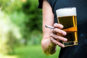 iemand houdt een sigaret en een glas bier vast