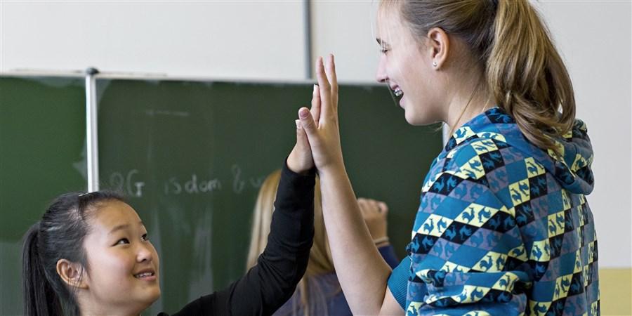 Een groot en een klein meisje vergelijken hun handen.