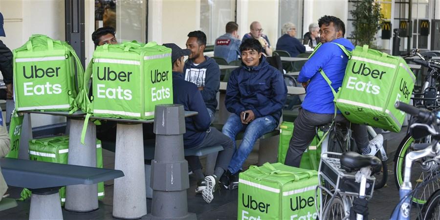 UberEATS fietskoeriers wachten op hun bestelling in het centrum van Den Haag
